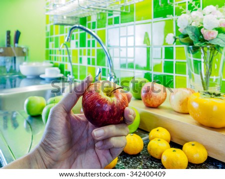 Hand holding apple over cabinet top in green modern kitchen/ Interior still-life - stock photo