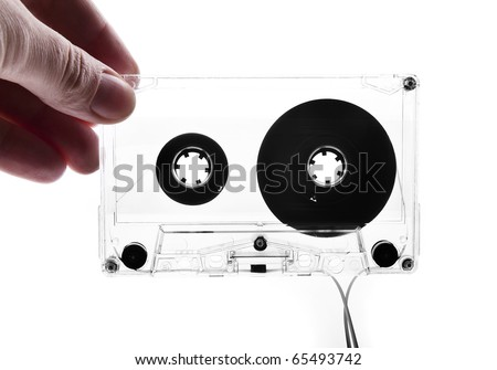Hand holding audio cassette - stock photo