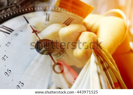 Hand holding bag and card and old vintage clock with color effect, time of shopping concept - stock photo