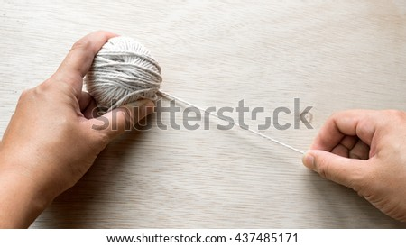 Hand holding ball of baumwolle yarn cotton wool on wooden floor surface. Slightly de-focused and close-up shot. Copy space. - stock photo