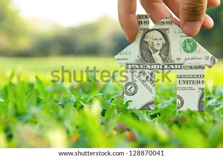 Hand holding banknote house icon,real estate concept. - stock photo