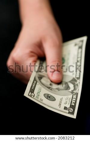 Hand holding 5$ banknotes. Small DOF. - stock photo