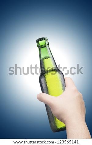 Hand holding beer bottle - stock photo