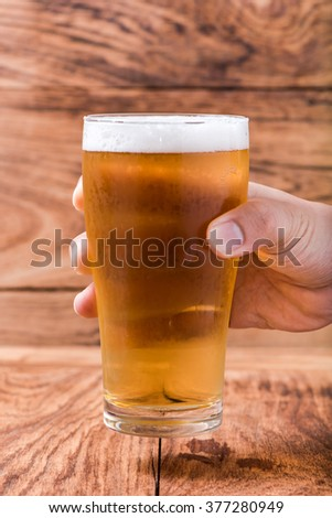 hand holding beer in mug glass on wood table