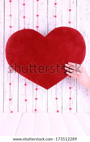 Hand holding big red heart on wooden background
