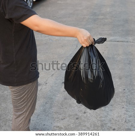 Hand holding black bag of rubbish - stock photo