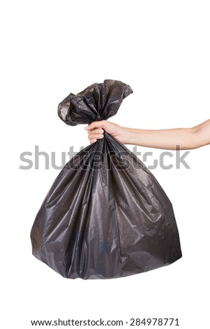 Hand holding black bag of rubbish on white background - stock photo