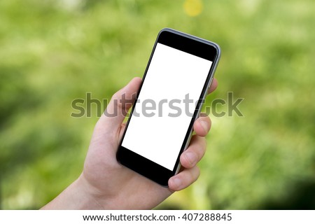 Hand holding black smartphone with blank screen against blurred grass background - stock photo