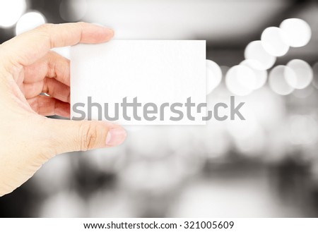 Hand holding blank business card with blur black and white  bokeh light background ,Business concept