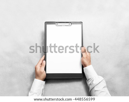 Hand holding blank clip board with white paper design mockup. Clear a4 document folder mock up template hold in arm. Clipboard notepad surface display front. Checklist tablet clamp file presentation. - stock photo