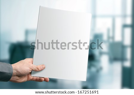 hand holding blank magazine with copy space at the office - stock photo