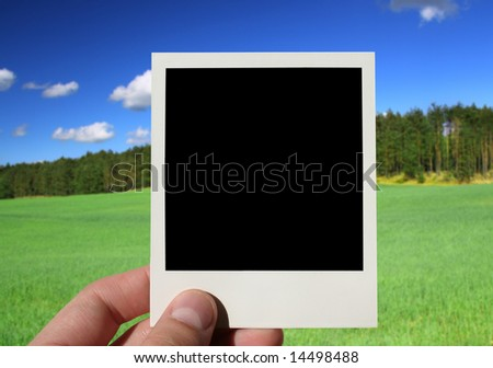 hand holding blank photo, beautiful countryside in background - stock photo