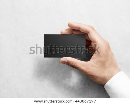 Hand holding blank plain black business card design mockup. Clear calling card mock up template hold arm. Visit pasteboard paper surface display front. Check small offset card print dark business card - stock photo