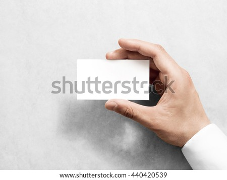 Hand holding blank plain white business card design mockup. Clear call id card mock up template hold arm. Visit pasteboard paper surface display front. Small pure offset namecard print. Logo branding - stock photo