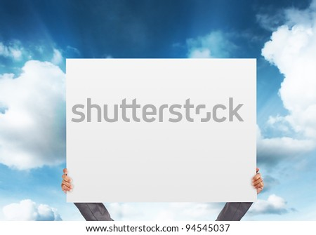hand holding blank Poster on blue sky background - stock photo