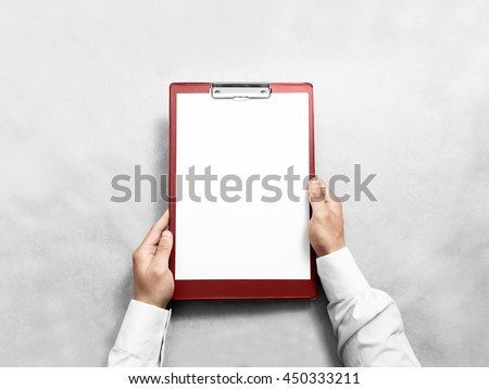 Hand holding blank red clipboard with white paper design mockup. Clear a4 document folder mock up template hold in arm. Clipboard notepad surface display front. Checklist tablet file presentation. - stock photo