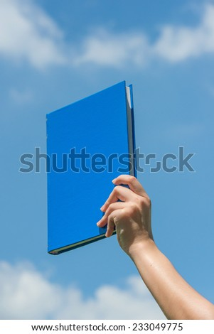 Hand holding book over blue sky - stock photo