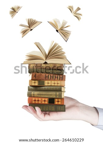 Hand holding book stack and books flying away isolated on white background. Education concept - stock photo