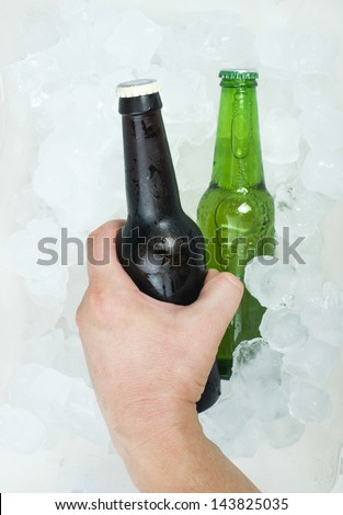 Hand holding bottle of beer and ice cubes - stock photo