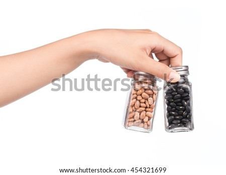 hand holding bottle of Pinto beans and black beans isolated on white background