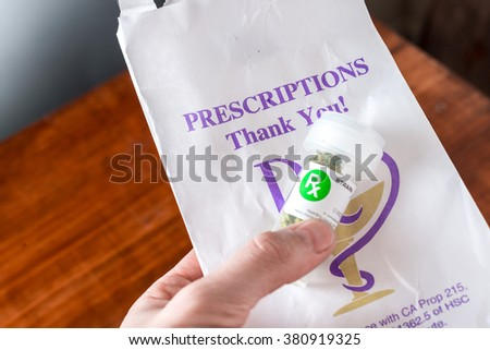 hand holding bottle with medical cannabis close up - stock photo