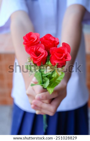 Hand holding bouquet of red roses