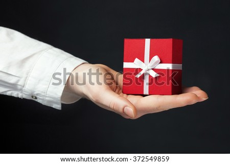 Hand holding box for a gift isolated on black - stock photo