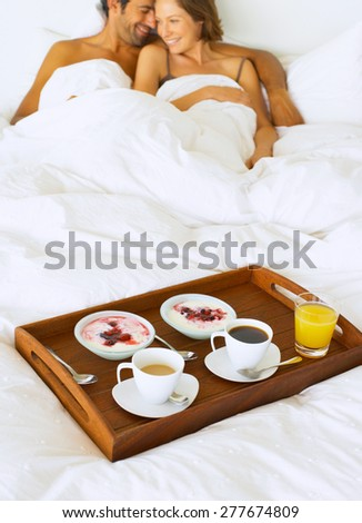 Hand holding breakfast in bed - stock photo