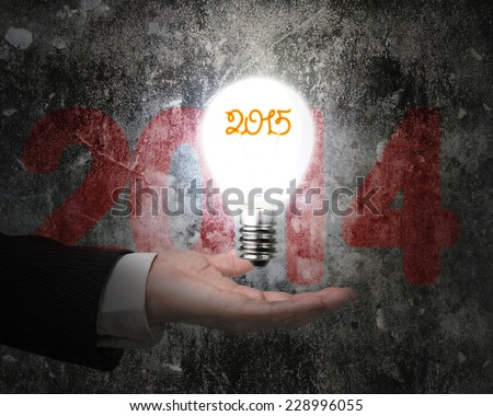 hand holding brightly 2015 light bulb illuminated old concrete wall with dark red 2014 word - stock photo