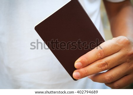 Hand holding brown blank passport - stock photo