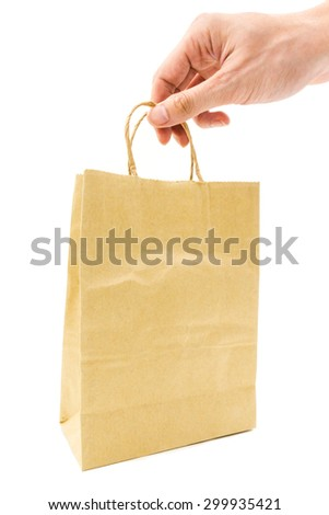 hand holding brown paper bag on white background - stock photo