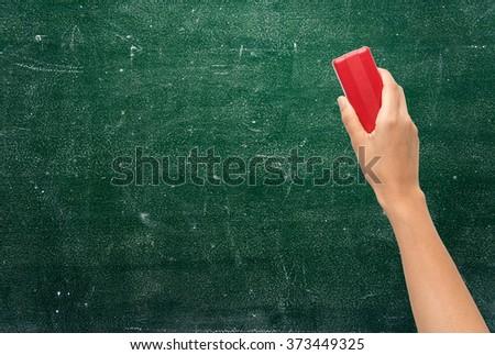 Hand holding brush erase on green chalkboard - stock photo