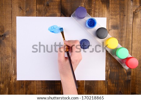 Hand holding brush with paints and paper on wooden background - stock photo