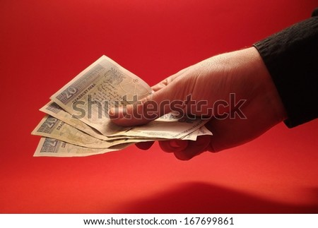 Hand holding Bulgarian money on red background - stock photo