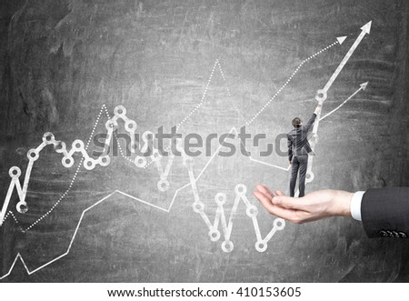 Hand holding businessman miniature drawing business chart on concrete wall - stock photo