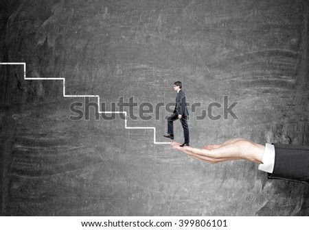 Hand holding businessman starting to climb stairs drawn on black wall. Concept of career growth. - stock photo