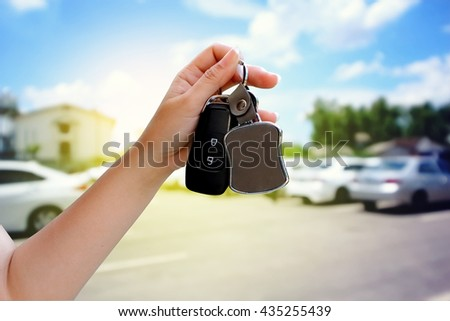 hand holding car key and tag with blur outdoor car park background