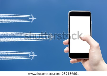 hand holding cellphone and airplane on a blue background - stock photo