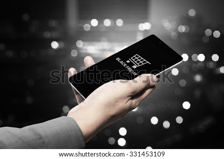 Hand holding cellphone with black friday text and shopping cart - stock photo