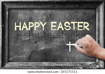 "Hand holding chalk and writing text ""Happy Easter"" on blackboard. - stock photo"