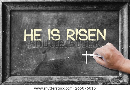 "Hand holding chalk and writing text ""He Is Risen"" on blackboard. - stock photo"