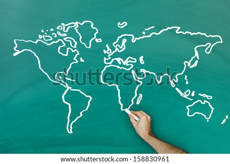 Hand holding chalk drawing world map on blackboard - stock photo
