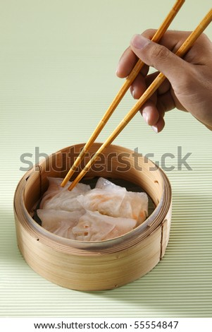 Hand holding chopstick reaching out for snacks. - stock photo