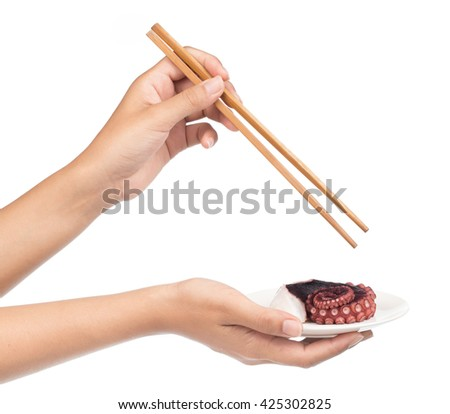Hand holding chopsticks, eating tentacles of octopus isolated on white background - stock photo