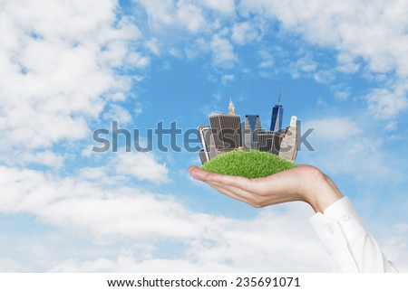 hand holding city on green grass hill - stock photo