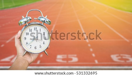 hand holding clock with blur running track background in healthy concept