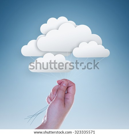 hand holding clouds on light blue background - stock photo
