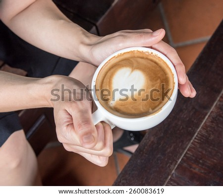 hand holding coffee cup above wooden table, top view coffee cup - stock photo