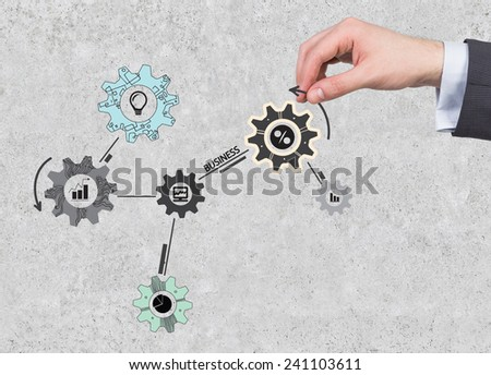 hand holding cogs and gears on wall background - stock photo