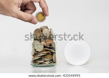 Hand holding coin with jar glass full of coins, and jar cap with copy space - stock photo